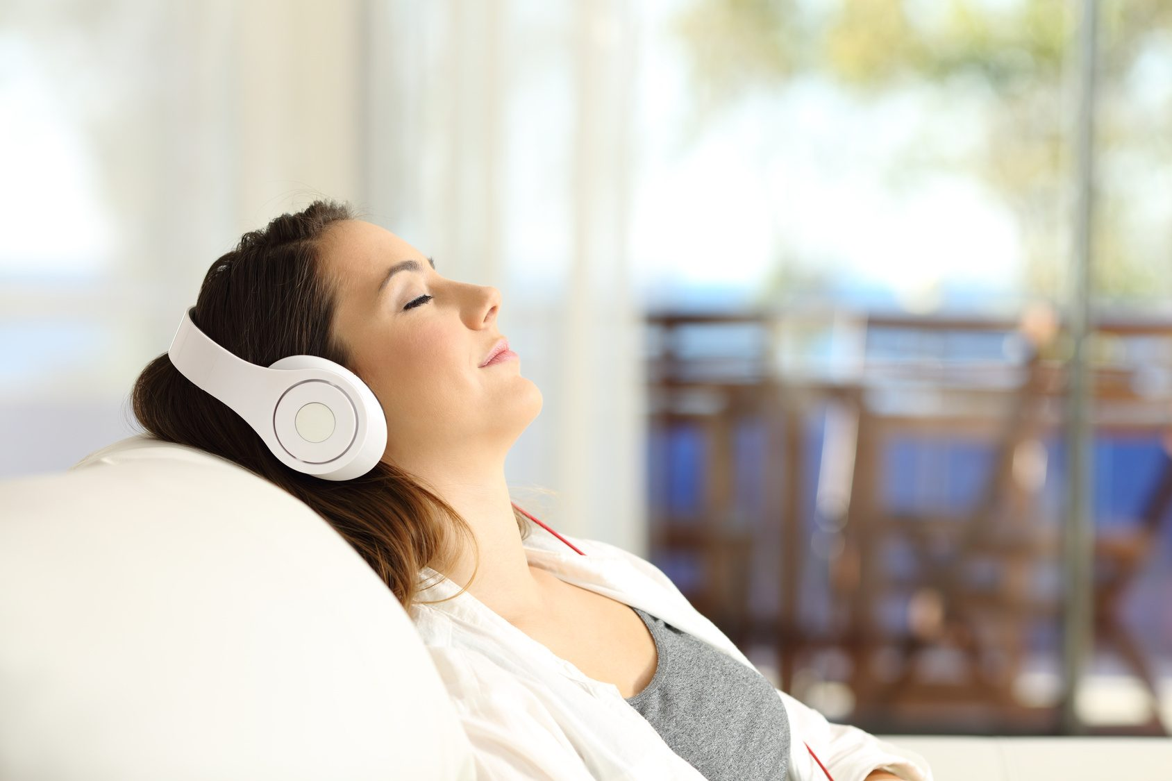 Side view portrait of a woman relaxing listening to music on a couch in the living room at home